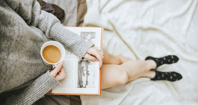 Woman reading with cup of coffee