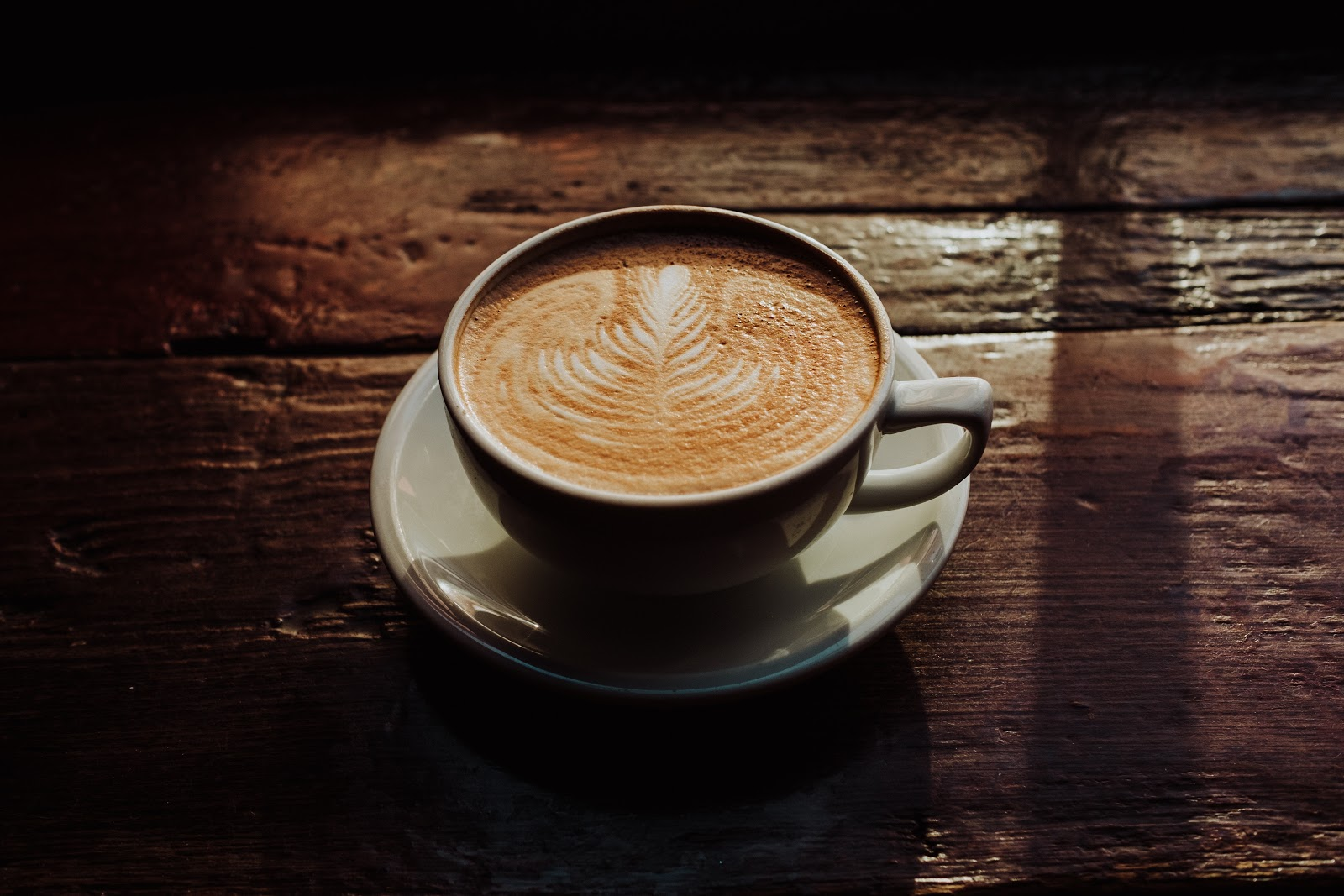 Latte sitting on saucer on a wood table