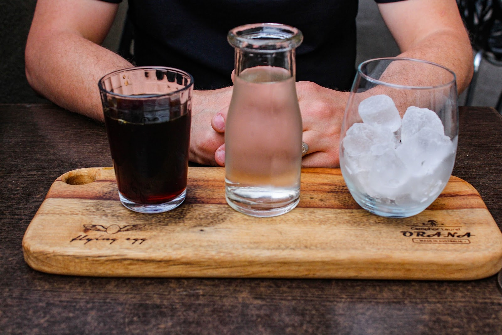 Glass of coffee, jar of water, and cup of ice on a wooden board