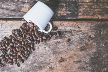 Coffee grinders: Coffee beans spilling out of a mug